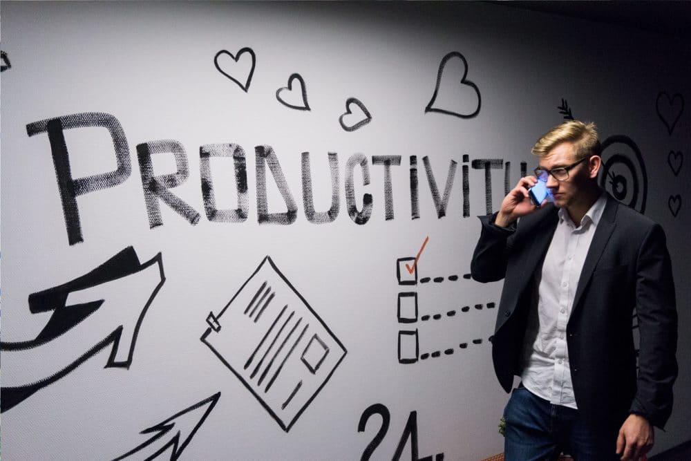 man standing in front of a wall that says productivity