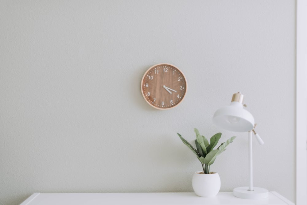 A lamp, plant and clock on white background.